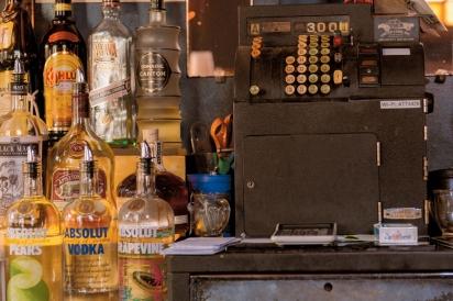 Older cash register and bottles of liquor